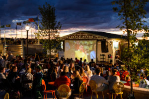 """People relax in a section of seating at the Memorial Union Terrace along Lake Mendota and watch """"National Lampoon's Animal House"""" as dusk falls to a summer night, shown on the Terrace's new performance stage."""